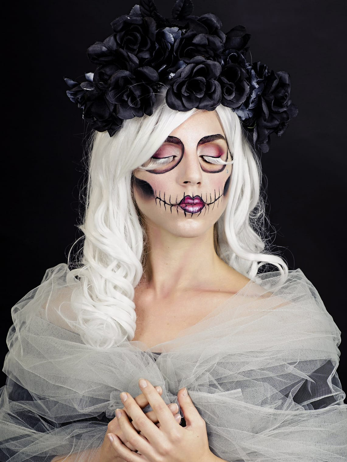 Woman, sugar skull makeup, white wig, black roses, white veil