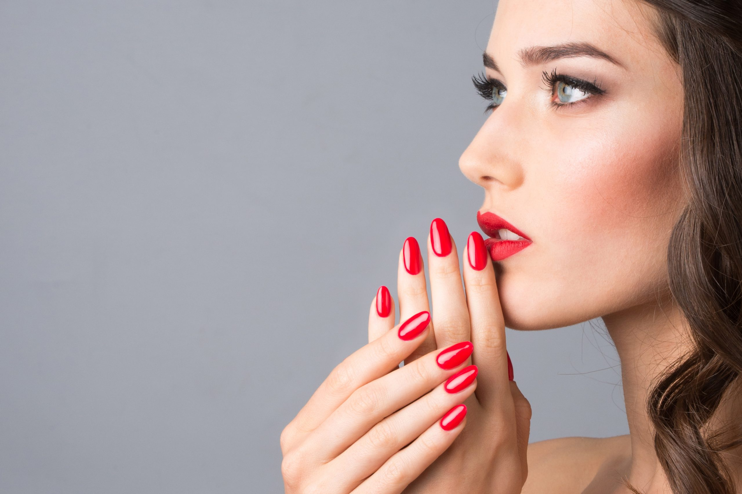 Blue-eyed Woman, red nails and lipstick, Closeup